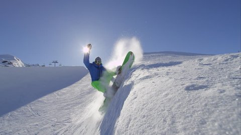 SLOW MOTION: Pro snowboarder riding the half pipe in big mountain snow park, sliding and spraying snow on the halfpipe wall in sunny winter. Extreme snowboarder snowboarding and performing tricks.