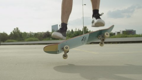 SLOW MOTION CLOSE UP: Unrecognizable skateboarder skateboarding and jumping ollie tricks on street. Extreme closeup of skateboarder's legs and sneakers jumping flip trick with skateboard outdoors.