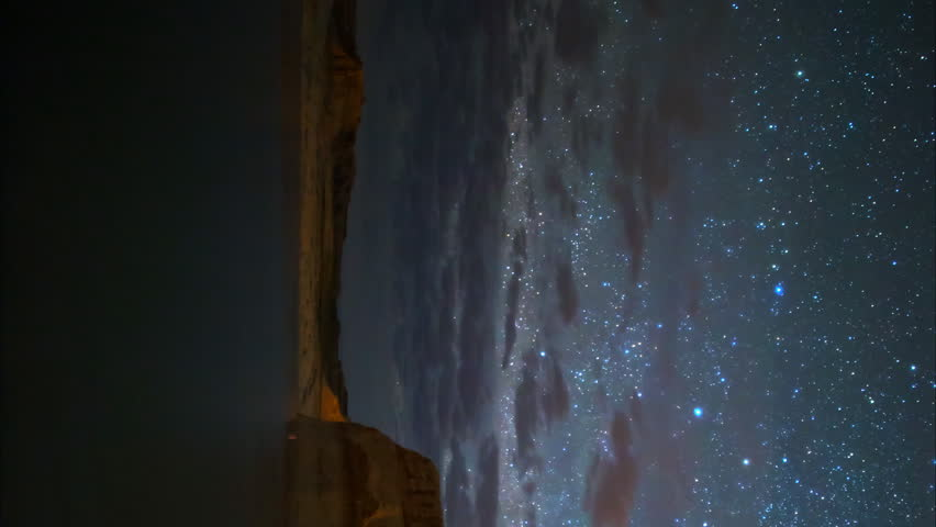 Astrophotography Time lapse with pan motion of starry sky over Lone Rock in Lake Powell, Utah -Vertical Shot-