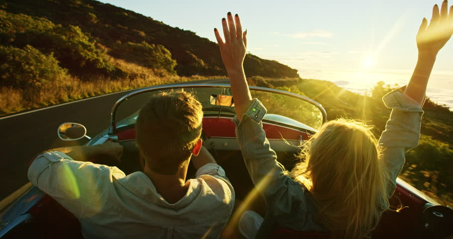 Happy couple driving on country road into the sunset in classic vintage sports car | Shutterstock HD Video #20219089