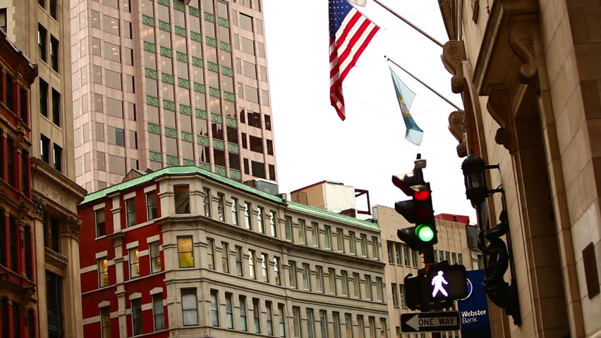 BOSTON, MASSACHUSETTS, USA - CIRCA 2011; Overcast daytime in downtown Boston, MA including buildings, flags, and stoplight