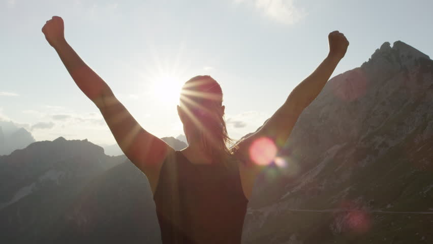 SLOW MOTION, CLOSE UP: Young female standing on the edge of the cliff and raising her hands up against high rocky mountains sunbathing in evening sun. Happy girl enjoying success and stunning view   Shutterstock HD Video #20240824