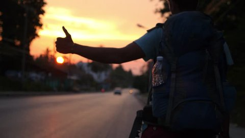 Traveller with Backpack Hitchhiking on Road Travel at Sunset