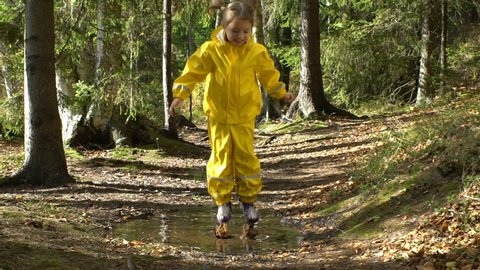 Little girl in a yellow rubber suit is jumping in a puddle. Slow motion.