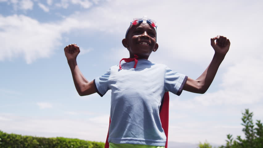 A young boy dressed in a homemade superhero costume raises his arms like a comic book hero. A golden light shines across him as he smiles. Bright, blue sky in the background. Low angle. Slow motion. | Shutterstock HD Video #20291719