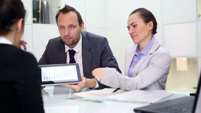 Business consultants explaining something on digital tablet to client