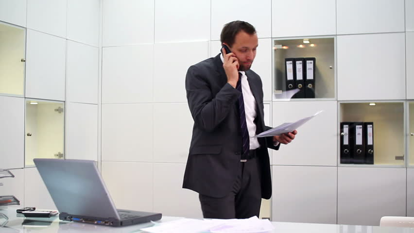 Businessman with documents talking on cellphone in modern office