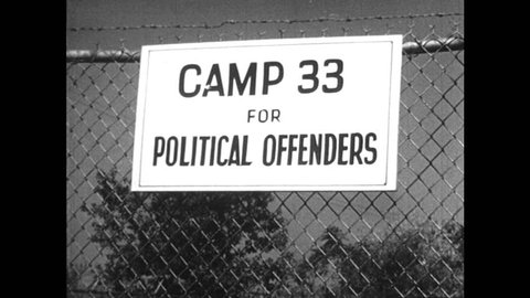 United States 1940s: Sign on barbed wire fence for 'camp 33 for political offenders'. Noose being fitted on hooded man. Flames on a burning cross. Man talks to camera as he points at poster