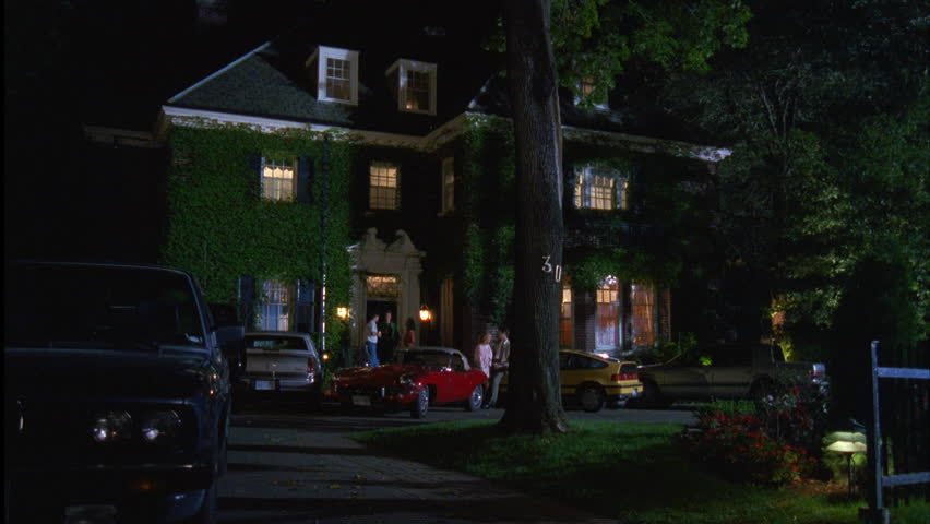 night tilt up upscale 3 story brick house mansion, dormers, ivy, many cars, party people hanging out front door couple leaning car, fraternity house
