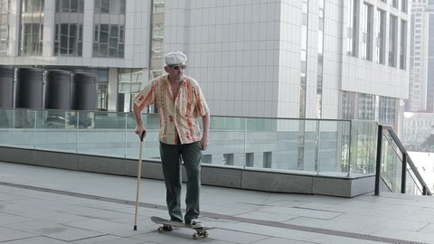 Old man with a cane riding on a skateboard.