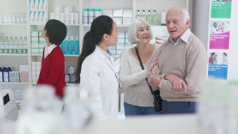 4K Worker in a chemist shop assisting elderly couple. Shot on RED Epic.