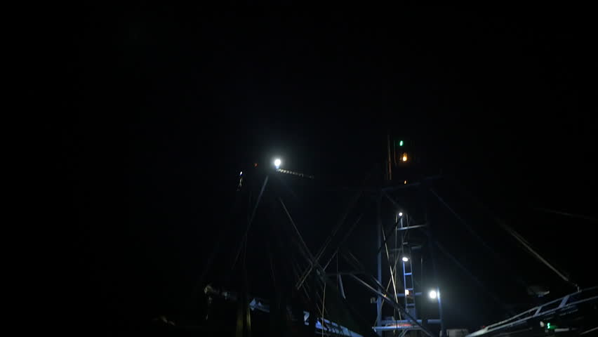 Pan up on shrimping trawler sailing out to sea to fish at night.