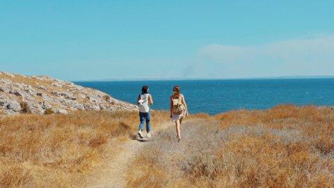 Slow motion of young female hiker walking somewhere on the coast of cape Kazantip
