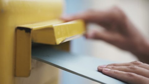 Woman is sending a blue letter into a yellow letterbox. 4K