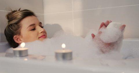 Side view of Caucasian woman taking bath in bathtub in bathroom