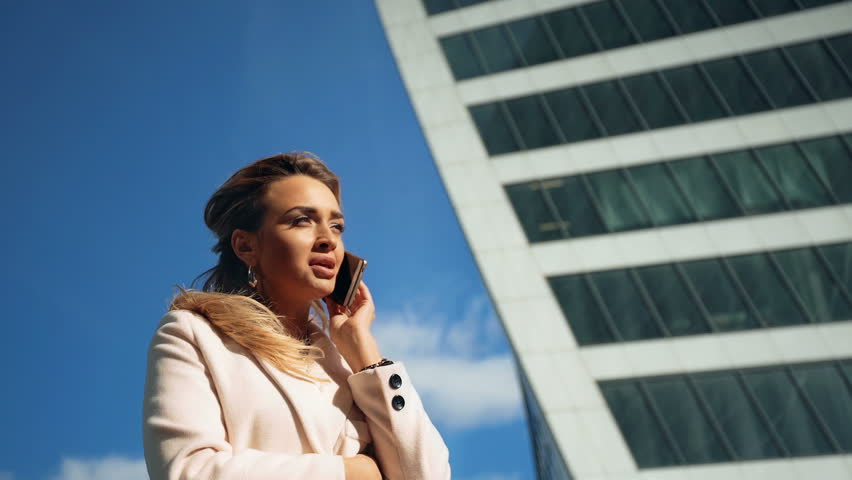 Beautiful young business woman calling by phone on the background of skyscrapers | Shutterstock HD Video #20491129