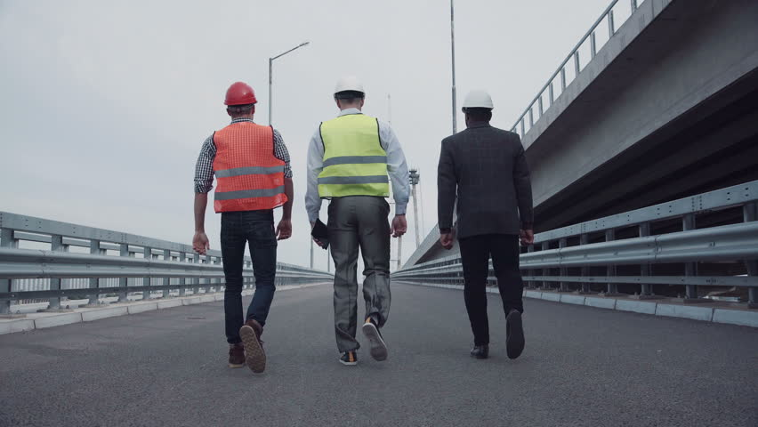 4K shot of Diverse group of three male construction engineers in white hard hats with reflective jackets walking on highway ramp. Rear view on road along bridge. | Shutterstock HD Video #20494693