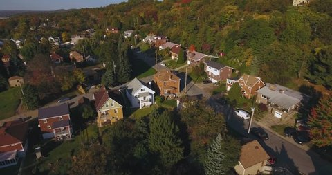 An aerial view above a small Western Pennsylvania town and neighborhood on an Autumn evening. Pittsburgh suburb.