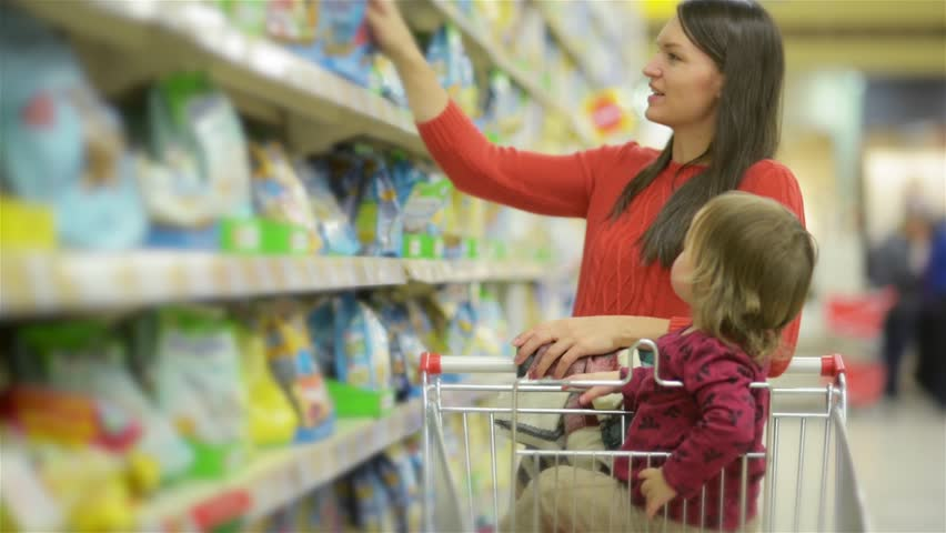Beautiful woman with baby daughter shopping in supermarket, young Mother chooses food for their child in the market