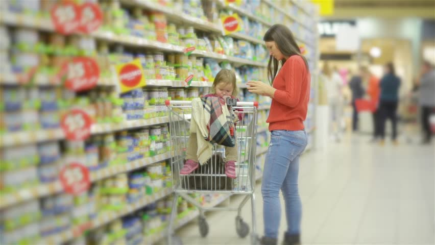 Beautiful woman with baby daughter shopping in supermarket, young Mother chooses food for their child in the market | Shutterstock HD Video #20534809