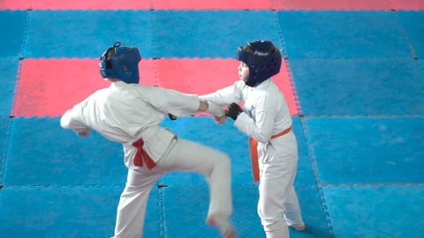 Kids karate competition. Fight a duel of teenagers. Children are protected and strikes the opponent. Young athletes are involved in a fight with courage.