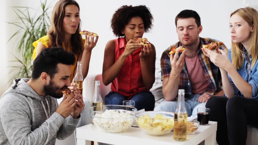 Friendship, leisure, fast food and celebration concept - happy friends with drinks and snacks eating pizza at home | Shutterstock HD Video #20553049