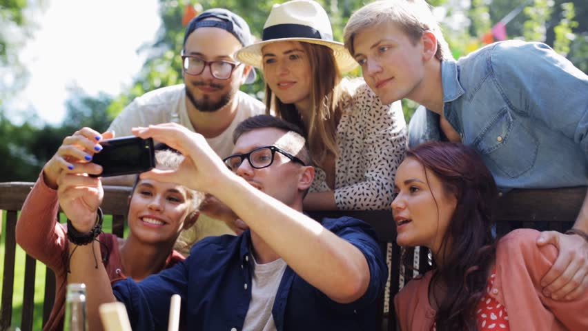 Leisure, party, technology, people and holidays concept - happy friends taking selfie with smartphone and gathering for dinner at summer garden party | Shutterstock HD Video #20553070