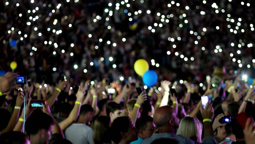 Kherson, Ukraine - 17 September 2016: open free charity concert in honor of the City Day. lot of people turn on the flashlight on mobile phones and other gadgets in Kherson, Ukraine - 17 September.