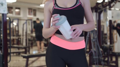 Attractive caucasian girl is drinking a protein shake drink in the gym 4K