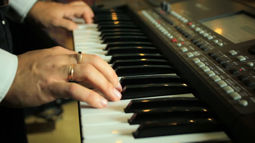 A man playing on a synthesizer electronic piano, hands close-up | Shutterstock HD Video #20592769
