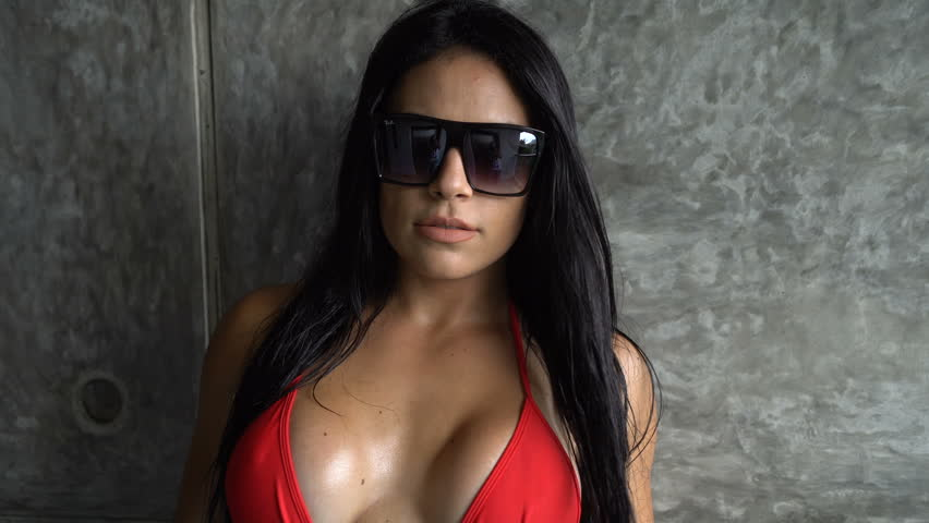 Beautiful brunette seductive woman in red bikini with sunglasses looking into the camera and posing against concrete gray wall background | Shutterstock HD Video #20598247