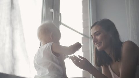 A Portrait of happy young mother with a baby at home kissing and laughing