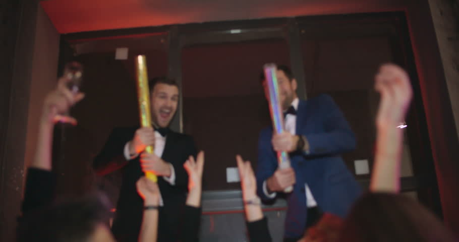 Shaky cam of tipsy gilded youth dancing in night club and laughing as two men in suits shooting confetti cannons over them