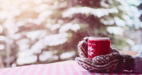 Hands in Knitted Mittens holding Steaming Cup of Hot Coffee or Tea on Snowy Winter Morning Outdoors. 4K DCi SLOW MOTION 120 fps. Woman holds Cozy Festive Red Mug with a Warm Drink on Christmas Morning