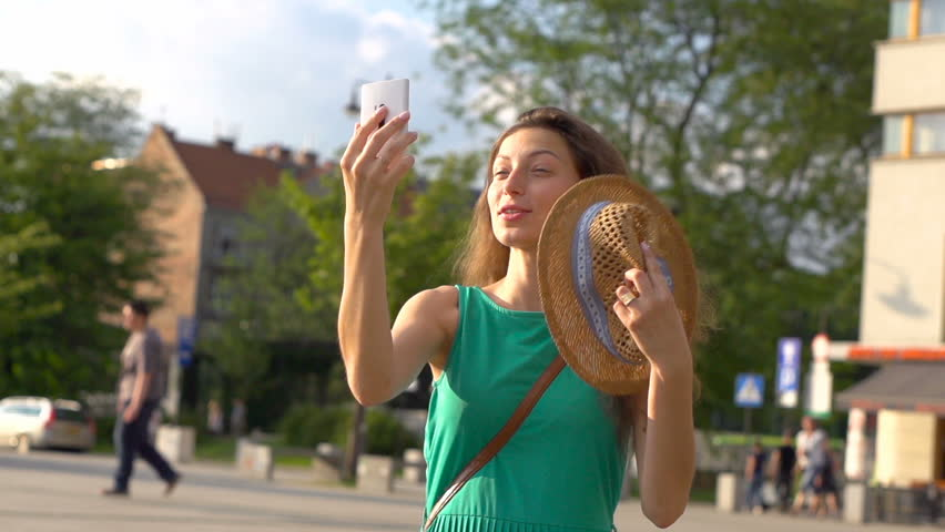 Girl chatting on cellphone and showing town to someone, steadycam shot, slow motion shot at 240fps  | Shutterstock HD Video #20638459