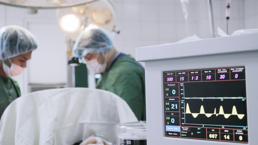 Anesthesia machine in use. Out of focus surgeons at the background.