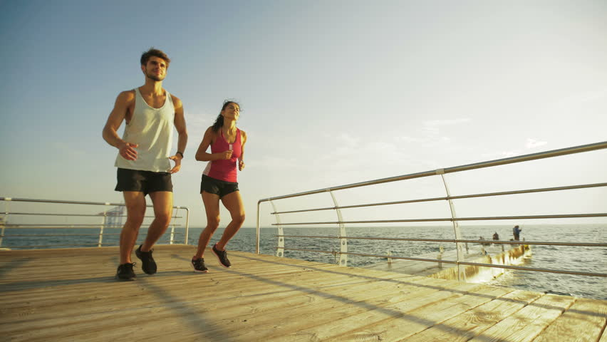 Young couple running on the wooden boardwalk. #20657629