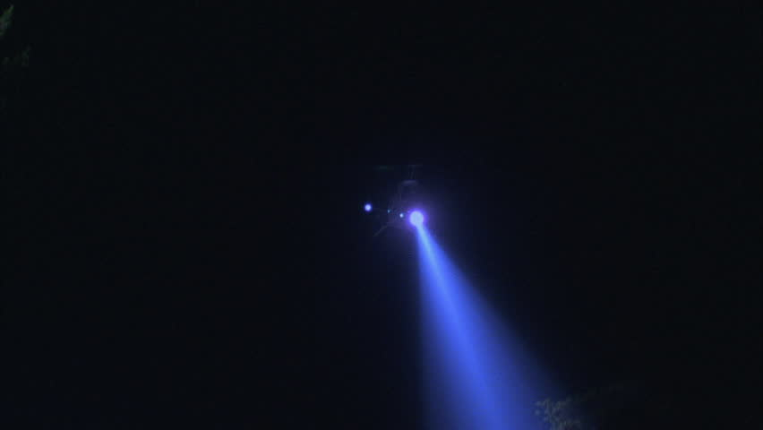 night ground air up blue white helicopter searchlight against sky only left right away could be police helicopter