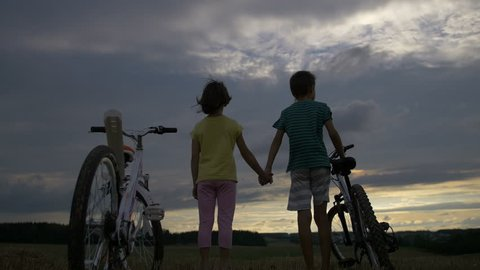 boy with girl with bicycles on the mountain in the evening holding hands
