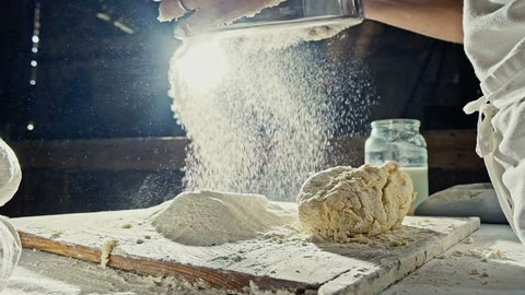 Mans hands sifting flour through a sieve for baking
