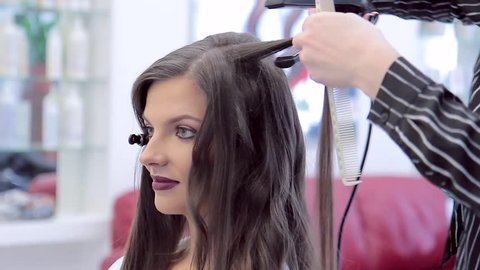 Beautiful smiling brunette in beauty salon, hairdresser is doing style her hair