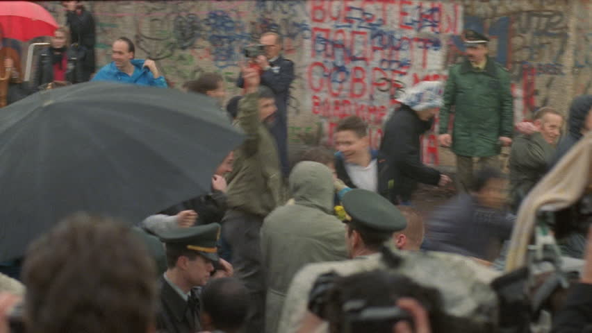 day down crowd celebrating near Berlin Wall, see photo flashes military soldiers, people running, light rain, umbrellas fall Berlin Wall, historical footage