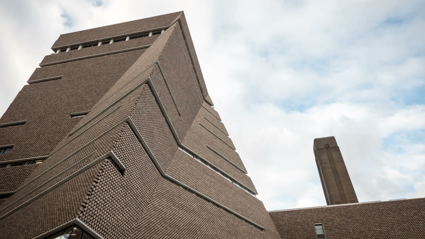 New Tate Modern extension, London. Low, wide angle time lapse video footage of the new extension to the Tate Modern art gallery in London, England, with its iconic chimney stack visible to the right.