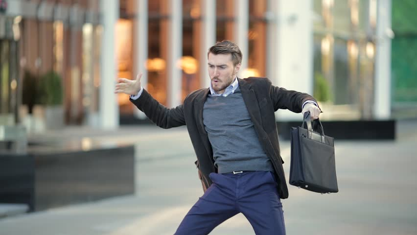 Attractive man with a beard and briefcase dancing in the street #20821549