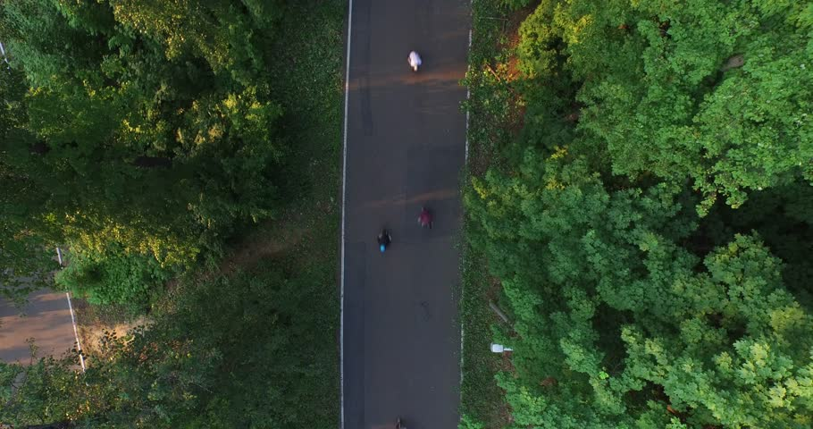 Mixed group of teenaged longboarders racing each other downhill on a mountain road