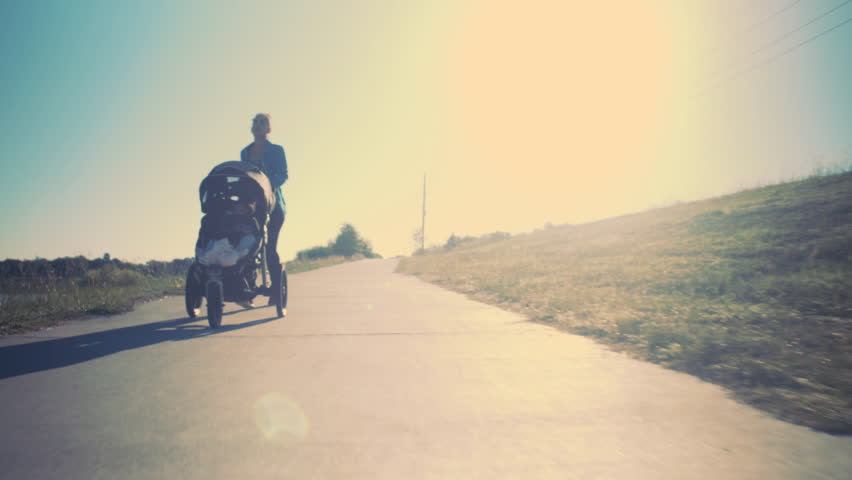 Bright sunshine behind a mom pushing her toddler in a stroller as she gets some exercise in an effort to stay fit and healthy.