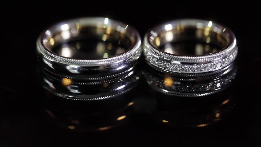 Wedding Rings Black Background Shining With Light Close Up Macro. Two Bride  And Groom Rings