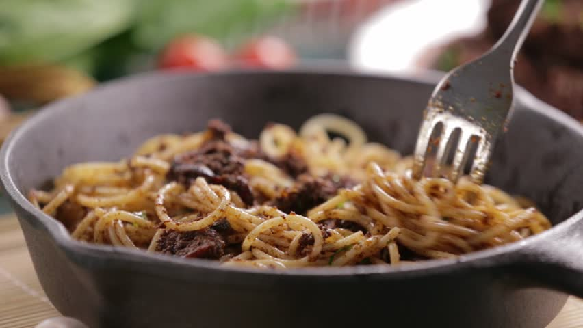 Eating beef and mushroom spaghetti pasta on a cast iron pan
