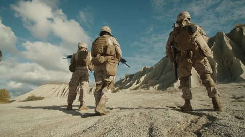 Follow Shot of Squad of Soldiers Running Forward During Military Operation in the Desert.  Shot on RED EPIC Cinema Camera in 4K (UHD).