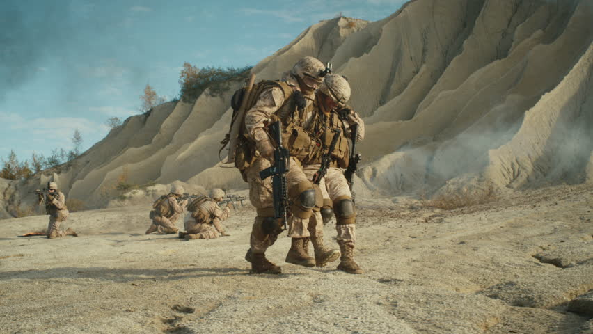 Soldiers Carrying Injured One While other Members of Squad Covering Them During Military Operation in the Desert. Slow Motion. Shot on RED EPIC Cinema Camera in 4K (UHD).
